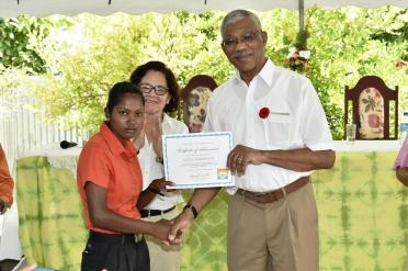 President David Granger presents the Certificate of Completion to this young lady, who was the lone female participant in the Electrical Installation Course