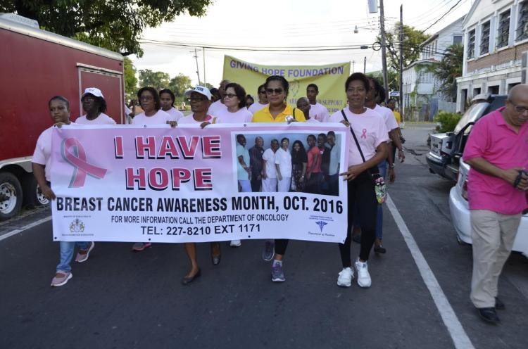First Lady, Mrs. Sandra Granger and representatives of other groups march through the city streets, this morning, to raise awareness about breast cancer