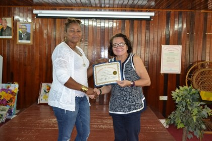 "Colleen Prince receiving her certificate from First Lady Mrs Sandra Granger. Colleen, who is a successful entrepreneur said, ""The workshop has been very beneficial [for me]. Mostly what I've learnt is the experiences that I've had here from other business people, the other women and the businesses they have, inspired me and give me more knowledge on how to create and improve my business."""