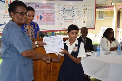 A student of St. Paul's Primary School receives her certificate of participation on the Leprosy awareness poster competition