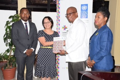 Minister of Finance Winston Jordan receives CHD Report from UN Resident Coordinator Mikiko Tanaka while UNDP Regional Advisor Kenroy and Deputy Vice Chancellor of the UG Dr Barbara Reynolds looks on