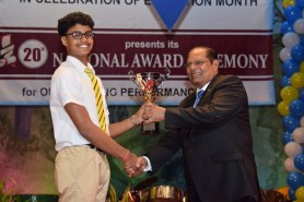 Kayshav Tewari of Queen's College collects one of his trophies from Prime Minister Moses Nagamootoo at the 2016 National Award Ceremony. Tewari won several awards including Best CSEC performer and the Best Outstanding Performer-Overall