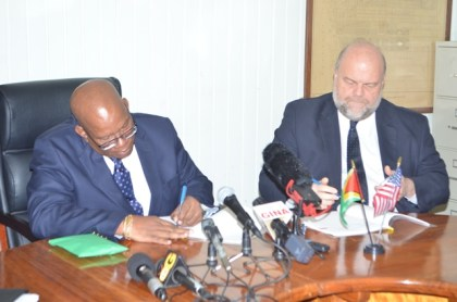 Hon . Winston Jordan Minister of Finance and Ambassador of the United States of America to Guyana, Perry Holloway signing the FATCA agreement at the Ministry of Finance, earlier today