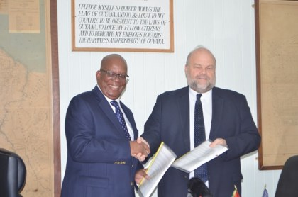 Hon. Winston Jordan Minister of Finance and Ambassador of the United States of America to Guyana, Perry Holloway displaying the  signed FATCA agreement at the Ministry of Finance, earlier today