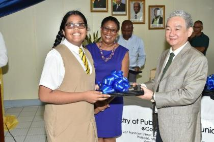 Chinese Ambassador, Mr. Zhang Limin presenting a first form Queen's College student with a laptop while Minister of Public Telecommunication, Ms. Catherine Hughes looks on