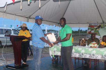 A farmer collecting his land lease from Deputy CEO of GKDA, Dr. Walrond Powered