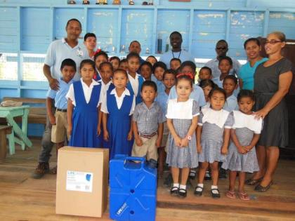 GWI officials pose with teachers and students of Karrau Creek Primary School who received water filters