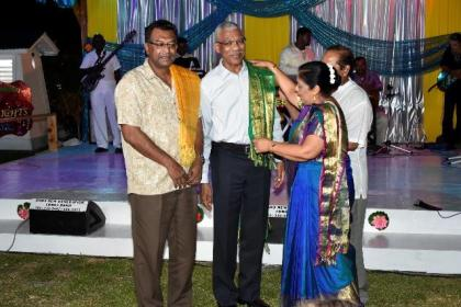 Mrs. Sita Nagamootoo presents a scarf she brought from a recent visit to India to President David Granger at the end of the event. Vice President Khemraj Ramjattan was also presented with a similar one.