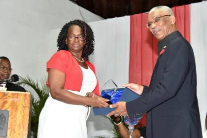 President Granger receives a token of appreciation from the Treasurer of the GTUC, Mrs. Kim Halley