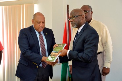 Minister of Natural Resources, Mr. Raphael Trotman (left) receives the interim report on the Commission of Inquiry (CoI) into the Rock Creek mining accident from Presidential Advisor on the Environment, Rear Admiral (ret'd) Gary Best.  Commissioner (Ag.) of the Guyana Geology and Mines Commission (GGMC), Mr. Newell Dennison is also pictured (partially) behind Advisor Best.