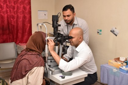 Head of GPHC's Ophthalmology Department, Dr. Shailendra Sugrim assisting Dr. Ronnie Bhola with a patient