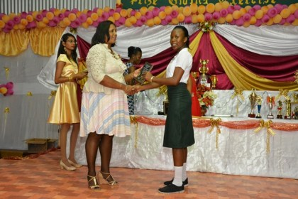 Most Outstanding Student at CSEC 2016, Ms. Ateisha Brand receives her plaque from one of the teachers at the graduation ceremony