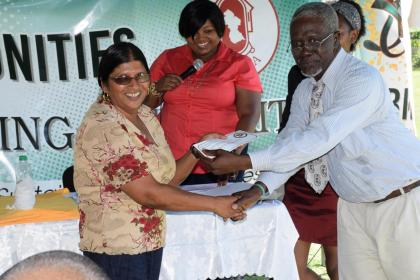 One of the beneficiaries from Berbice receiving her Home Improvement Voucher from a Regional Official