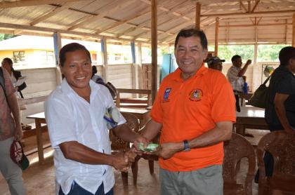 Minister of Indigenous Peoples' Affairs, Sydney Allicock handing over the money to Treasurer of NRDDB, Lakeram Haynes