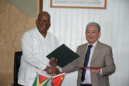 Minister of Finance, Winston Jordan, and outgoing Ambassador of the People's Republic of China, Zhang Limin exchanging the signed Framework Agreement for the East Coast Road expansion