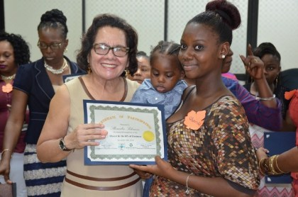 First Lady, Mrs. Sandra Granger helps Ms. Shemika Solomon to display her certificate as she holds her son, at the graduation ceremony of the Self Reliance and Success in Business Workshop for women