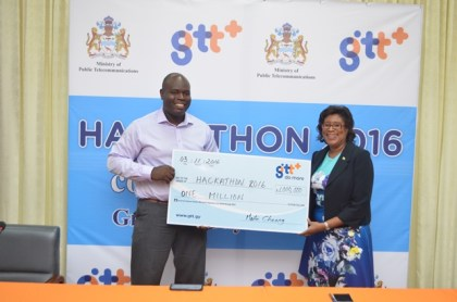 Justin Nedd, Chief Executive Officer of the Guyana Telephone and Telegraph Company (sponsor of the Hackathon) handing over cheque to Minister of Public Telecommunications, Catherine Hughes