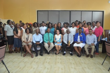 First Lady, Mrs. Sandra Granger (centre) is flanked by (from left, seated) Lieutenant Colonel (ret'd) Yvonne Smith, of the Office of the First Lady, Mr. Wayne Barrow, facilitator at Interweave Solutions Incorporated, Region Ten Mayor, Mr. Carwyn Holland, Regional Chairman, Mr. Renis Morian, Ms. Sandra Adams, Assistant National Director of Community Development Council and Mr. Yohann Sanjay Pooran, facilitator at Interweave Solutions Incorporated. The participants are pictured standing.