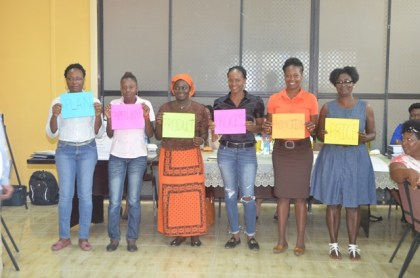Some of the women display placards featuring the 'Six Ps' of Business, today, at the 11th Self Reliance and Success in Business Workshop for women in Upper Demerara-Berbice (Region 10).