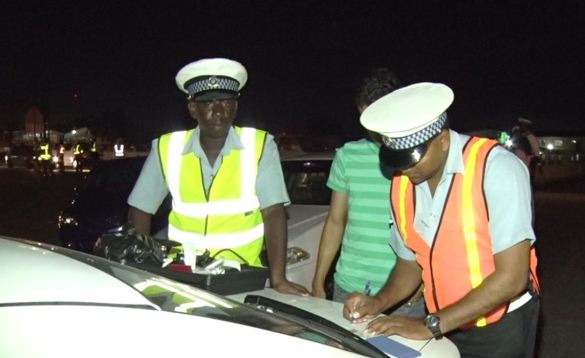 Officers recording the information off a breathalyser after conducting a test on a driver
