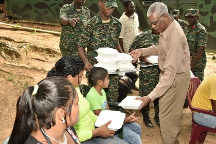 President Granger serving lunch to some of the villagers, who were present at the event today.