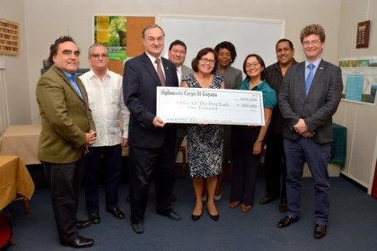 Dean of the Diplomatic Corps, Russia's Ambassador to Guyana, Mr. Nikolay Smirnov and First Lady, Mrs. Sandra Granger display the symbolic cheque valued US$1,000 that Members of the Diplomatic Corps donated to her office in support of its Shoes that grow programme. Also in picture, from left to right: Chile's Ambassador to Guyana, Mr. Claudio Rojas Rachel, Cuba's Ambassador to Guyana, Mr. Julio César González Marchante, Mexico's Ambassador to Guyana, Mr. Ivan Robero Sierra Medel, Ms. Sharon Patterson of the Ministry of Social Cohesion, UN Resident Coordinator and UNDP Resident Representative, Ms. Mikiko Tanaka, Mr. Dane Gobin, Treasurer of the Diplomatic Corps and CEO of the IIC and British High Commissioner to Guyana, Mr. Greg Quinn