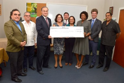 Dean of the Diplomatic Corps, Russia's Ambassador to Guyana, Mr. Nikolay Smirnov and First Lady, Mrs. Sandra Granger help Ms. Sharon Patterson, Programme Coordinator of the Ministry of Social Cohesion, to display the symbolic cheque as other members of the Diplomatic Corps look on.