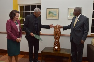 President David Granger, accompanied by First Lady, Mrs. Sandra Granger handing over the gift of a wooden sculpture called the 'The Chief Witness to the Environment' to Prime Minister Freundel Stuart.