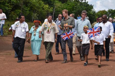 Prince Harry interacts with Minister of Indigenous Peoples Affairs, Sydney Allicock. Also in photo are British High Commissioner to Guyana, Greg Quinn (blue shirt, left of Prince Harry).