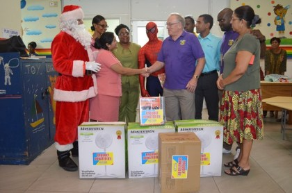 Director of Operations at Courts, John Standaloft handing over presents to a staff of the Georgetown Public Hospital Corporation (GPHC)