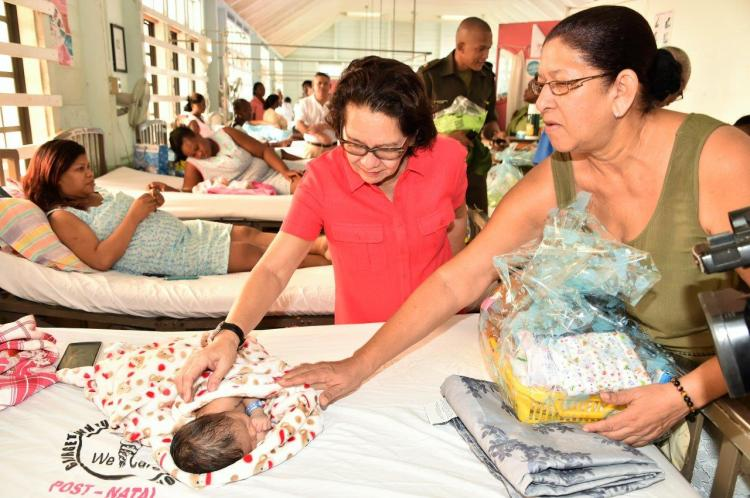 First Lady Mrs. Sandra Granger and GPHC's Public Relations Officer, Ms. Mitzy Campbell seem quite taken by this little one in postnatal care