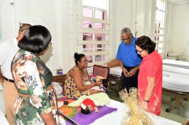 President David Granger and First Lady Mrs. Sandra Granger take a moment to admire this Christmas baby who is sleeping peacefully