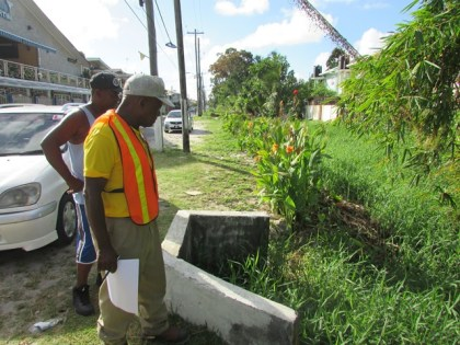 MPI's Community Coordinator, Neilson McKenzie (with reflective vest), inspects the Lamaha Canal during a recent walkabout of Newtown, Kitty. The Lamaha Canal is one of several spots identified for major works in the coming weeks