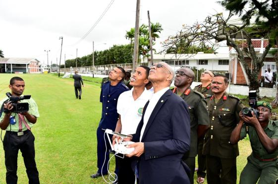 President David Granger manning the controls of the drone camera
