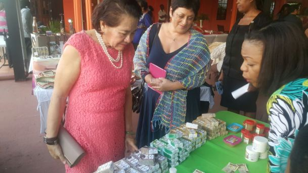 First Lady, Mrs. Sandra Granger and Ms. Andrea De Caires, President of Tourism and Hospitality Association of Guyana (THAG) examining some of the products on display at the exhibition