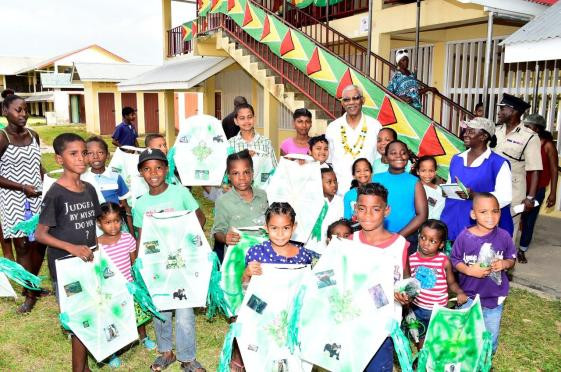 Big Smiles! President David Granger poses with the children of the Parika-Salem community