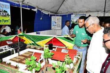 President David Granger listens as Mr. Frank Blair, Project Manager of the Regional Democratic Council's Multi-purpose self-sustainable farm describes the elements of the model to him