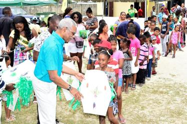 President David Granger distributing kites to these eager children