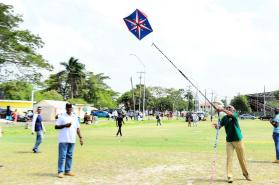 Up, up and away! President David Granger successfully raises a kite in the National Park on Easter Monday
