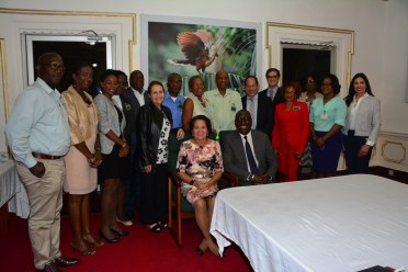 First Lady, Mrs. Sandra Granger and Mr. Clifford Samuel, Senior Vice President, Gilead Sciences Incorporated (pictured seated) along with the participants of the meeting, which was held in the Conference Room at State House
