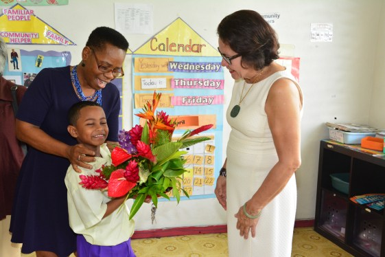 Tutor Ms. Cheryl Welch assists student Rizwan Valz as he presents First Lady, Mrs. Sandra Granger with a bouquet in gratitude for her visit