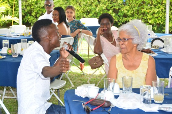Mr. Mark Batson serenades this patron at the WAD Easter Hat Show and Brunch held in the garden of the Critchlow Labour College