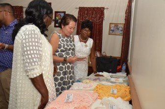 First Lady, Mrs. Sandra Granger is pictured here examining several items made by Ms. Mabelene McDonald and Ms. Claudette Ralph
