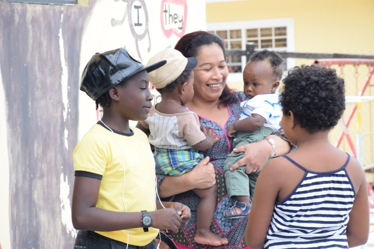 Minister within the Ministry of Communities, Dawn Hastings-Williams interacting with children