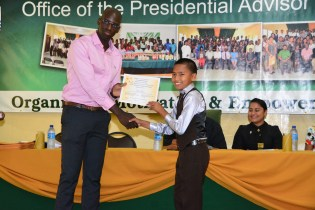 Twelve year old Fenny Adrian is the youngest graduate of the programme. He proudly receives his certificate from Mr. Ronald Austin, Senior Education and Training Officer at the Office of the Presidential Advisor on Youth Empowerment