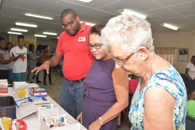 General Secretary of the GRCS, Mrs. Dorothy Fraser, First Lady, Mrs. Sandra Granger and GRCS First Aid Coordinator, Mr. Devaughn Lewis examine some of the First Aid boxes prepared by the participants during the workshop