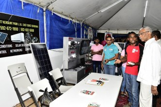 President David Granger listens as Head Field Technician, Mr. Akiem Yanvield describes the solar panel sale and installation services offered by Smart Tech Solutions at the West Berbice Expo