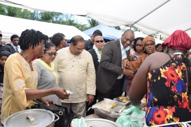 Acting President, Prime Minister Moses Nagamootoo, and Minister of State Joseph Harmon interacting with food vendors at the Cultural fest.