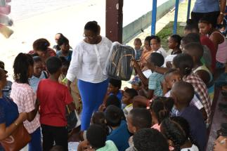 Minister Broomes distributing school supplies to children from Bartica