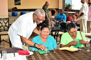 President David Granger points out a particular feature on one of the coins that he presented to the ladies, who were honoured at a special luncheon, which was held in the dining room of The Rupununi Eco Hotel.
